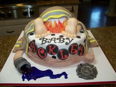 Firefighter baby rump cake - Strawberry cake w/ bc icing, covered in fondant.  The rump is also cake.  Feed and legs are made from AUI chocolate fondant and is super yummy and easy to sculpt with.  Holds it form nicely too!  Gumpaste accents and fondant firejacket.  I used isomalt for the water coming out of the fire nozel.