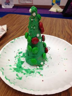 Holdiday activity for kindergarten, first grade, second grade or any grade! Sugar ice cream cones, green frosting, m&ms, and sprinkles are all you need. My first graders loved it! #christmastree #DIY #firstgrade #teacher #students #arts #crafts #food #snack