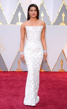 2017 Oscars: Priyanka Chopra is wearing a silver strapless Ralph & Russo gown with a square neckline and square design detail. I like the texture of this dress. The color pops really well against her skin!