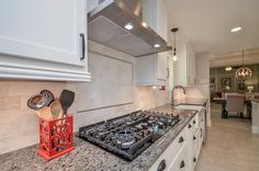 22306 Rebecca Burwell Ln, Katy, TX: Photo A gorgeous brushed marble subway tile backsplash flows up to the crown molding above the sink, with a herringbone design above the cooktop. Dark gray granite shines in contrast to the white cabinets. It's all about the details in this kitchen!