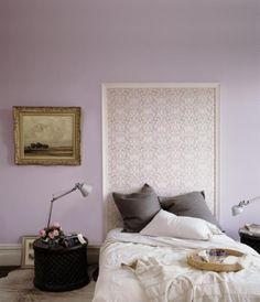 Tête de lit avec du papier peint et un cadre en bois.