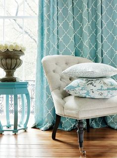 In love with those aqua colored shades, pillows and side table.