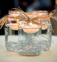 Mason jar centerpieces with floating candles. [UPDATED These DIY Mason Jar Centerpieces can also be made into favors. Use the lanterns to provide light to your wedding tables. Floating Candle Centerpieces, Rustic Wedding Centerpieces, Diy Centerpieces, Easy Table Decorations, Quinceanera Centerpieces, Wedding Tables, Wedding Ceremony, Floating Candles Wedding, Wedding Cake