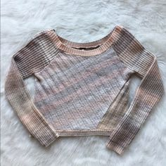Free People cropped sweater Light pink and grey patterned long sleeve. Super cute and cozy for any outfit! Great condition! Fast shipping! Free People Sweaters