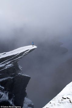 Emma and friend Mark peering over the sheer edge of the Trolltunga in Norway and another tourist, Luis, standing looking out at the misty fjords Daredevil, Stunts, Cliff, Troll, Yoga Poses, Norway, Ps, Brave, Travel Destinations