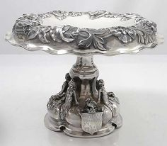 "Pr Antique English Sterling Fruit Compotes  A pair of large impressive English silver compotes each with four cast and applied figures on the pedestal base. Hand chased floral decoration on the canopies and the bases. Each has heraldic crest bolted to the base. Never monogrammed. Weight: 57.75 troy ounces. Height: 7 1/2"". London 1875. Maker Alexander Macrae"