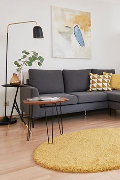Check out this beautiful Mic-Century inspired living room with a grey couch and yellow accents. We love the styling of your designer Sascha. Check out our website to find more inspiration!