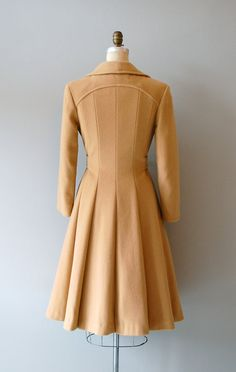 vintage 1970s camel wool belted trench with open collar, princess cut from the waist down, gored back for lovely skirt look and tons of movement, slender sleeves, tie belt (no other closures) and interesting pintucked detail. fully lined - a heavy wool coat that is great for cold weather.    ✂-----Measurements    fits like: small/medium  shoulder: 15  bust: up to 38  waist: belt ties waist  hip: free  sleeve: 22  length: 42  brand/maker 100% wool w/Woolmark label  condition: excellent    ✩…