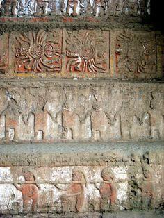 Cultura Moche: Mural en la Huaca de la Luna. Se puede apreciar en relieve algunas imágenes como una deidad en la parte de arriba, unos sirvientes en la segunda fila, y finalmente en la parte de abajo, se aprecia a un grupo de guerreros.