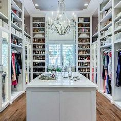 Gorgeous walk-in closet with hardwood floors, crystal droplets chandelier, marble top island for accessories, open shelving for shoes and clothes | EJ Interiors