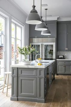 Grey and white kitchen...white, possibly Calcutta marble?, natural wood flooring and clear refrigerator