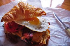 Fluffy Croissant with Crispy Bacon, Hashbrowns, Cheese, Fried Tomato and Sunny Side-Up Egg
