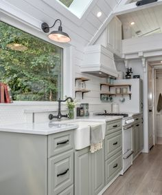 The kitchen include a farmhouse sink, gas stove, quartz counters, full size refrigerator, range hood, and pantry.