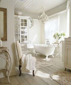 Alluring shabby chic bathroom in all shades of white. Floral rugs gives it a cozy warm vibe.