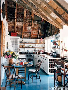 A charming cottage on Nantucket Harbor, decorated by Gary McBournie, features simple plank flooring painted Benjamin Moore's Deep Ocean and spattered in red, white, and blue. For decorative detail, McBournie studed vintage boating psoters and old photographs. The wooden grills of the kitchen cabinets were taken from an old photo of a 1920s yacht.