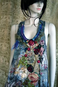There are fabrics and trims dating back 1930 to modern age. The base is vintage viscose and cotton blend tunic, hand dyed in shades of blue, teal, gray.. The front has composition of authentic antique textiles and laces, silk brocade applique in bronze hand beaded frame, vintage trims, sequin beaded red rose and hand sculpted silk blooms along embroidered rosebuds. Delicate blue silk tulle, handmade needle lace.. The bottom edge is trimmed with hand dyed tulle flounce. Versatile piece can be…