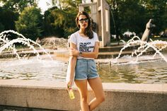 Elisa from www.schwarzersamt.com is wearing a casual freetime look with a white JUNIQE shirt,  vintage denim shorts in blue and white Birkenstick Arizona. It was shoot in the sundown in the city park.