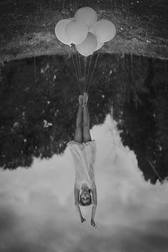 flying? standing on balloonS? Hanging upside down... It's a photograph in black & white