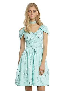 The mint fit and flare chiffon dress has an allover foil print with images of Ariel's silhouette, seaweed, shells and Flounder. Drape cold shoulder sleeves top off a faux wrap V-neck bodice with a pleated waist that leads into a flowy skirt.