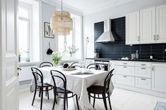 Scandinavian inspired kitchen with dark blue backsplash, white cabinents, and a wicker pendant light