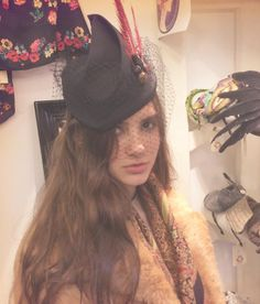 Saturday at the shop - Tilly wearing one of our black pleated hats with veil and red feathers. #BlackHat #BlackHatWithVeil #SaraTiara #PortobelloRoadShop #MadeInEngland #Handmade