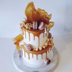 2 tier white buttercreme & caramel drip cake with macarons, popcorn & cascading toffee shards