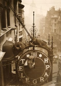 Workmen dismantle the clock which hangs outside the Daily Telegraph building at 135 to Fleet Street, London, The building is due to be remodelled. (Photo by Puttnam/Topical Press Agency/Hulton Archive/Getty Images) Old London, Vintage London, London Pubs, London City, Retro Vintage, Black White Photos, Black And White Photography, Vintage Photographs, Vintage Images