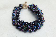 A Black Rain Bracelet, handmade with black crystals and colorful beads.