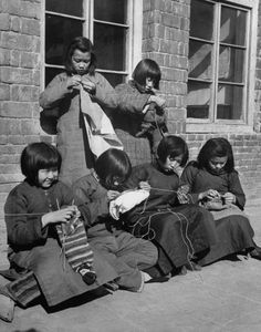Young girls knitting, probably at school or in an orphanage