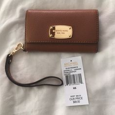 NWT Michael Kors IPhone 6 Wristlet MUST SELL PRICE DROP. NWT Michael Kors IPhone 6 Wristlet. Never used. Purchased in Nov 2015. Comes with tag. Brownish Tan color.  Will ship same day (if possible). (Price firm) Michael Kors Bags Clutches & Wristlets