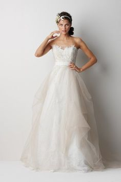 """Style Sydney Ivory sculpted strapless antique rose patterned, re-embroidered lace dress with oatmeal tulle overlay and ivory lace appliqué on bodice. Waist is accentuated with ivory grosgrain ribbon and train is 58"""" Sweep train."""