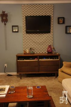 Hide Your TV cords by building a frame with fabric you like on it... Ingenuity. What about with wainscoting... Hmmm...