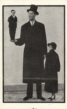 World's tallest man holds the world's shortest man on his palm while a woman of normal height stands next to him? I think?