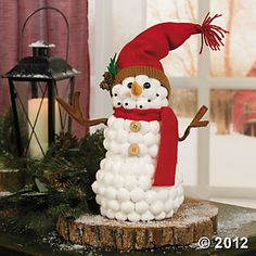 """Cotton Ball Snowman  This soft and smiling snowman decoration will make any table or mantel a little more cheerful. His jaunty scarf and broad smile will bring the holiday spirit into your home! Place this Christmas decoration around your home or give it as a Christmas gift for friends and family. Cotton. 12""""H x 12""""W with arms stretched out. $ 15"""