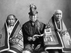Three leaders of the Chilkat, a Tlingit group, wear ceremonial dress for a potlatch. They hold ceremonial rattles, and two wear Chilkat blankets, which were woven of cedar bark and decorated with clan crests.