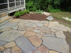 "A great example of well put together ""uncut"" flagstone of various sizes. Mixed colours add charm and beauty to this project. The bed will eventually fill in as well which will compliment the stone patio. Picture compliments of www.goshenstonework.com"