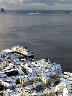 Cruise Hurtigruten at dock in Ålesund, Norway. This Norwegian Coastal Voyage starts out in Bergen and takes you across the Arctic Circle to Kirkenes in Finnmark, closely following the coast of Norway over a distance covering some 4,000 kilometers.