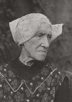 Mevrouw E. de Boer-Puik uit Laren in daagse dracht met 'ronde muts'. Ze draagt een schort met bovenstuk. 1952 #Laren #Gooi #NoordHolland #rond