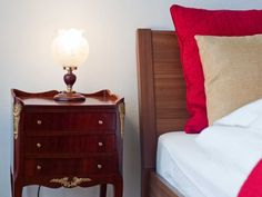 Elegant Vienna holiday rental apartments. Concerto Apartment, red and gold bedroom with antique night tables.
