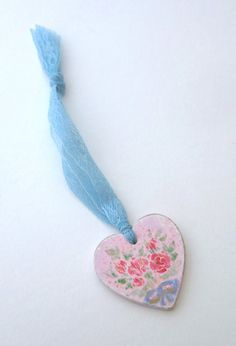 Hand-painted shabby pink heart with red roses, hanging from blue lace ribbon