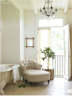 chair and ottoman, chandelier, juliet balcony with french doors and claw-foot tub