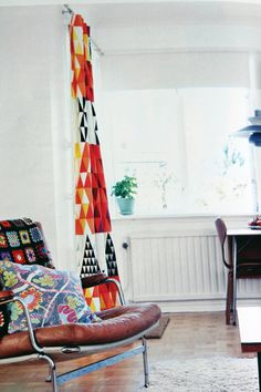 page from Swedish interiors magazine featuring vintage chrome & leather chair and colurful vintage fabric curtain  Looks pretty cosy to me