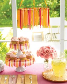 Use coordinating colors of seam binding to make flirty skirts for a pair of stacked cake stands, and then continue the theme with a free-flowing chandelier.