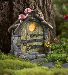 Miniature Fairy Garden Solar Light Up Hand-Painted Tree Door with Mushrooms 5 W x 2 D x 9.75 H. Invite fairies to your garden with this magical Miniature Fairy Garden Solar Door with Mushrooms, designed just for them! The resin door shines after dusk through the window, emitting a soft glow within your garden. Hand-painted details bring this little door to life. It features a distressed, faux-wood construction, a window, a stone frame and a pointed log roof with mushrooms on top...