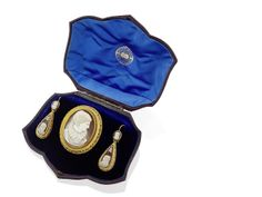 A Victorian suite of shell cameo jewellery depicting Mary, Queen of Scots, retailed by Aitchison, Edinburgh Comprising an oval brooch set with a brown and white shell cameo carved to depict Mary, Queen of Scots in profile, the bloomed gold frame decorated with scalloped wire and bead-work detail and with glazed locket compartment to the reverse, the pear-shaped earrings of complimentary design with hook fittings.