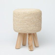 """Made Goods A petite ottoman made of a round raffia pillow top and bleached round teak legs. The raffia is a natural chalky white and has been crocheted. Finish: Raffia Dimensions: 14""""d X 19.5""""h"""