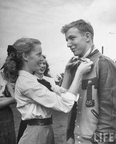 Teenage girl tying a scarf around the neck of her boyfriend as a fad. Atlanta, 1947.  By Ed Clark