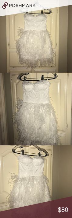 all white , sequin / feather dress from Bebe Pall white feather & sequin dress from Bebe perfect for Prom / banquet. Had an elastic band all around to hold up great area only worn once bebe Dresses Strapless