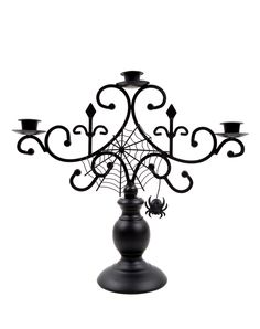 Spider Candelabra - Add the right kind of spooky flavor to your haunted house when you top a table with this Spider Candelabra. The all black metal candle holder features a creepy spider web design and a hanging mini spider. Make this creepy crawly candelabra yours for $19.99.