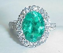 Platinum traditional ring with 8.20c fine green oval Columbian emerald with brilliant cut prong set accent diamonds 1.31c total weight.